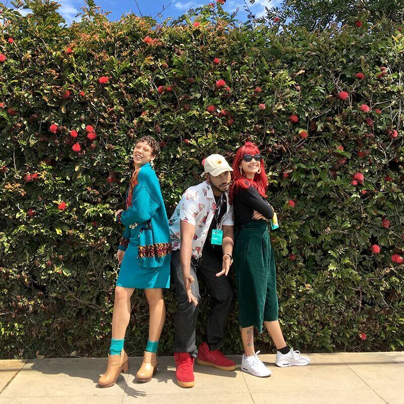 Three people posing in front of a rose bush with clothing from Buffalo Exchange.
